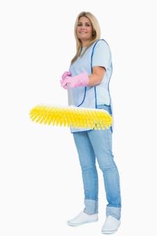 Uśmiechnięta czysta kobieta trzyma żółtą miotłę