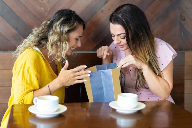 Uśmiechnięta dama pokazuje zakup przyjaciel w kawiarni