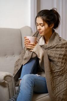 Uśmiechnięta dama w eleganckim modnym stroju siedzi na fotelu z filiżanką herbaty.