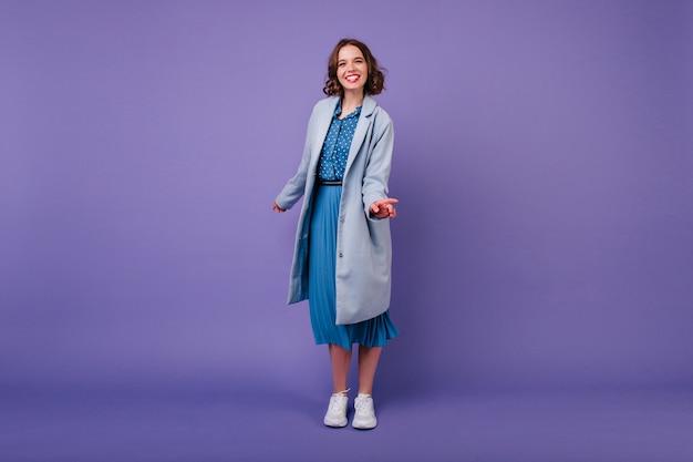 Uśmiechnięta dama w eleganckim niebieskim płaszczu. kryty portret śmiejącej się krótkowłosej dziewczyny w białych butach na białym tle na fioletowej ścianie.
