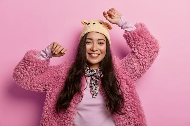 Uśmiechnięta, delikatna młoda kobieta tańczy zwycięstwa, czuje się optymistycznie i radośnie, trzyma ręce uniesione, nosi czapkę i futro, czuje smak sukcesu