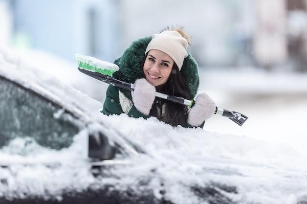 Uśmiechnięta, dobrze ubrana kobieta trzyma skrobaczkę i miotłę śnieżną, opierając się o samochód pokryty śniegiem.
