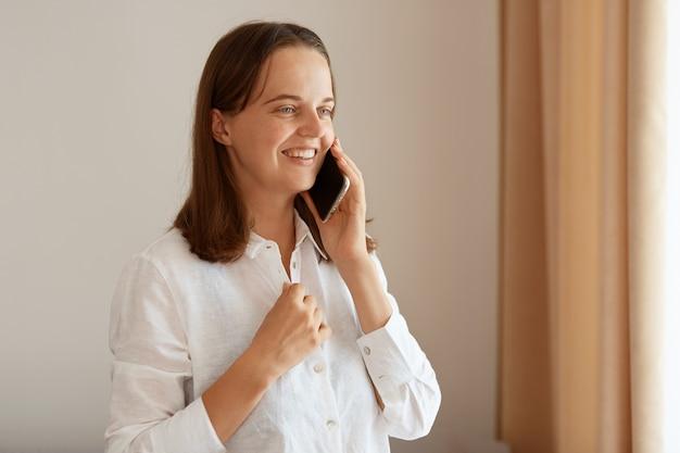Uśmiechnięta, dobrze wyglądająca kobieta o ciemnych włosach, ubrana w białą bawełnianą koszulę, rozmawiająca przez smartfon, mająca pozytywny wyraz twarzy, stojąca przy oknie z beżowymi zasłonami.