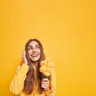 Uśmiechnięta, dobrze wyglądająca kobieta z wesołym wyrazem twarzy skupiona na górze, z radością trzyma smaczne lody w kształcie rożka, myśli o czymś przyjemnym, słuchając muzyki przez słuchawki pozuje na żółtej ścianie