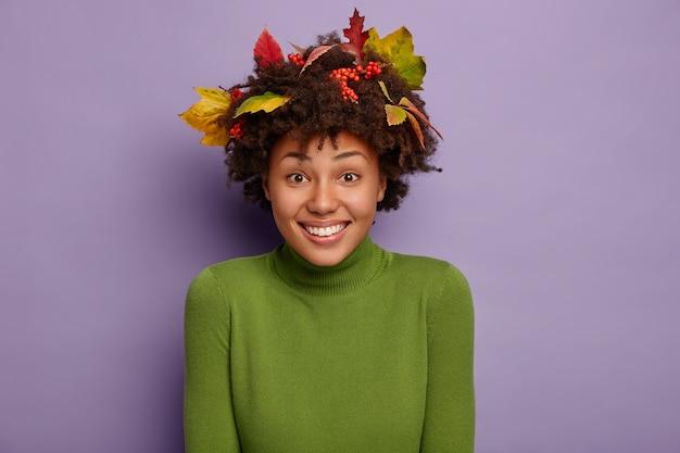 Uśmiechnięta, dobrze wyglądająca, kręcona kobieta jest w dobrym nastroju, radośnie patrzy na aparat, nosi zielony golf, jesienne opadłe liście na głowie, odizolowane na fioletowej ścianie