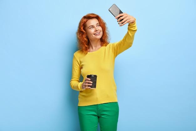 Uśmiechnięta, dobrze wyglądająca rudowłosa kobieta robi selfie na nowoczesnym telefonie komórkowym, aby przesłać ją do sieci społecznościowych