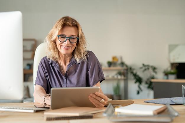 Uśmiechnięta dojrzała bizneswoman używa touchpada do surfowania po sieci w poszukiwaniu danych online, siedząc przy stole i pracując w domu