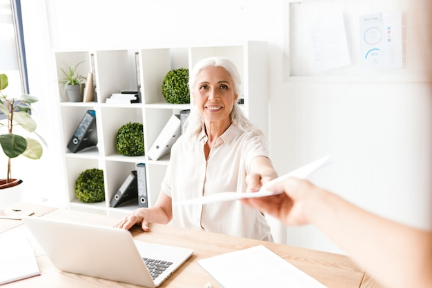 Uśmiechnięta dojrzała busienss kobieta daje dokumenty