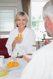 Uśmiechnięta dojrzała kobieta ma śniadanie z cropped mężczyzna