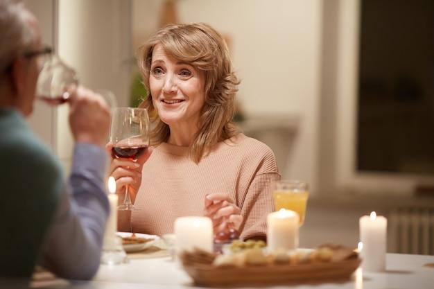 Uśmiechnięta dojrzała kobieta mówi do mężczyzny, jedzenie posiłku i picie wina przy stole w domu