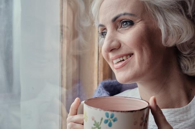 Uśmiechnięta dojrzała kobieta pije herbatę i patrzy przez okno, blokada i koncepcja izolacji, selektywna ostrość