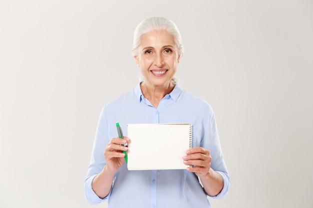 Uśmiechnięta dojrzała kobieta pokazuje notatnika z kopii przestrzenią dla teksta odizolowywającego