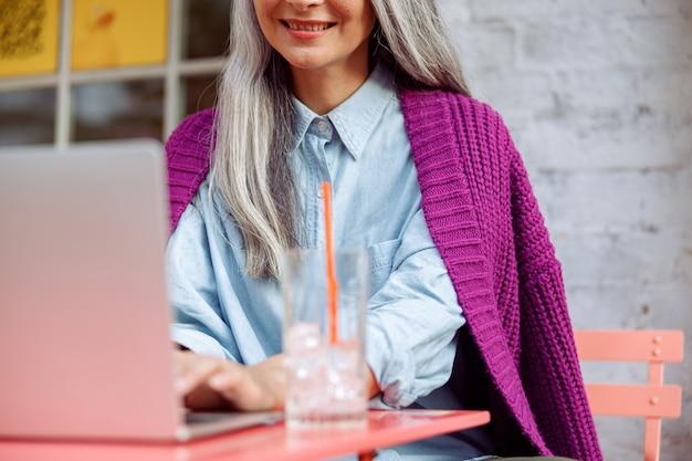 Uśmiechnięta dojrzała kobieta pracuje na laptopie, siedząc przy kolorowym stole na tarasie kawiarni