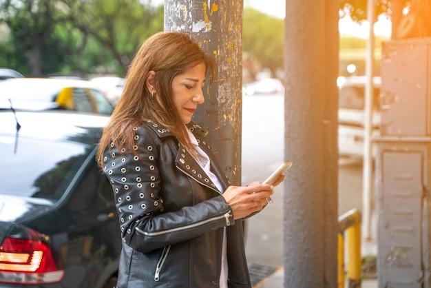 Uśmiechnięta dojrzała kobieta używa jej smartphone
