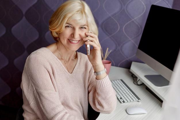 Uśmiechnięta dojrzała kobieta używa telefon komórkowego podczas gdy pracujący komputerem w domu