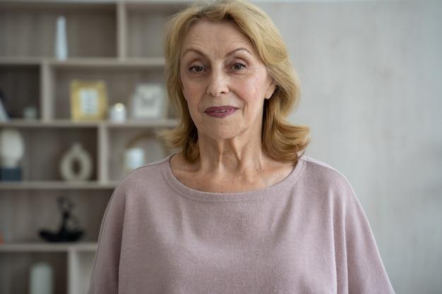 Uśmiechnięta dojrzała siwowłosa kobieta w średnim wieku patrząca w kamerę szczęśliwa starsza pani pozuje w domu