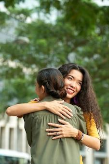 Uśmiechnięta dorosła azjatycka córka z kręconymi włosami przytula matkę w letnim parku podczas spotkania z nią