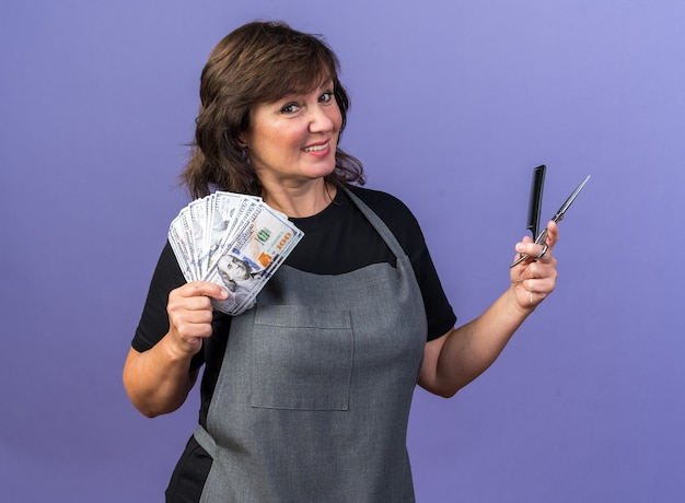Uśmiechnięta dorosła kaukaska fryzjerka w mundurze trzymająca grzebień i nożyczki na fioletowym tle z miejscem na kopię