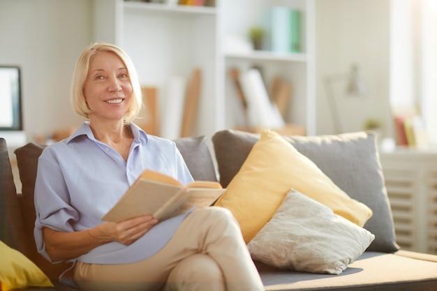 Uśmiechnięta dorosła kobieta, czytanie książki
