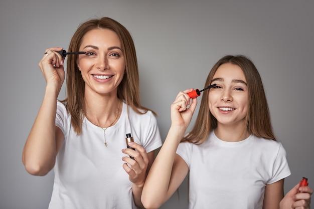 Uśmiechnięta dorosła kobieta i preteen córka nakładają tusz na rzęsy podczas wspólnej sesji kosmetycznej na szarym tle