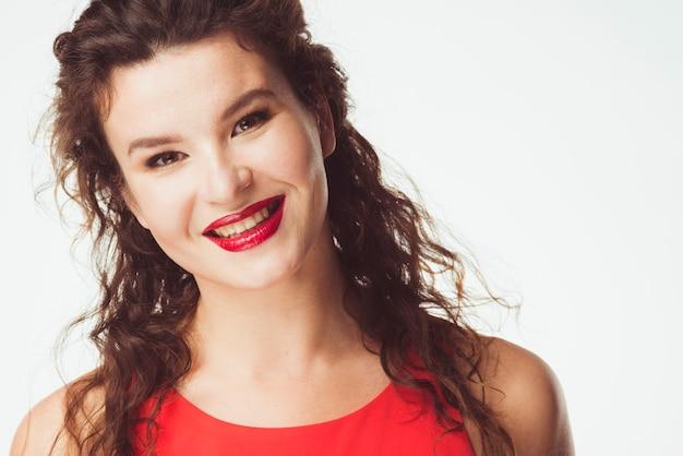 Uśmiechnięta dorosła kobieta w czerwieni sukni