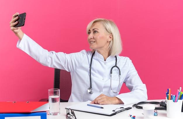 Uśmiechnięta dorosła lekarka w szacie medycznej ze stetoskopem biorąca selfie na telefonie siedząca przy biurku z narzędziami biurowymi odizolowanymi na różowej ścianie z kopią przestrzeni