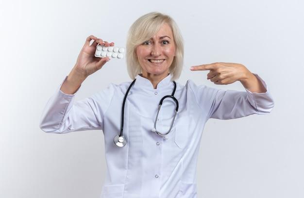 Uśmiechnięta dorosła lekarka w szacie medycznej ze stetoskopem trzymająca i wskazująca na tabletkę z lekiem w blistrze na białym tle na białej ścianie z miejscem na kopię