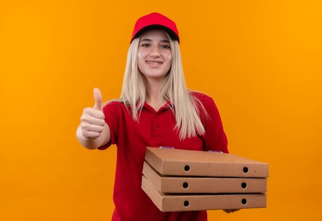 Uśmiechnięta dostawa młoda dziewczyna ubrana w czerwoną koszulkę i czapkę w ortezie dentystycznej trzymając pizzę bax jej kciuk w górę na odosobnionym pomarańczowym tle