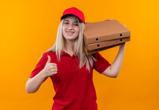 Uśmiechnięta dostawa młoda dziewczyna ubrana w czerwoną koszulkę i czapkę w ortezie dentystycznej trzymając pudełko pizzy na ramieniu jej kciuk do góry na odosobnionym pomarańczowym tle