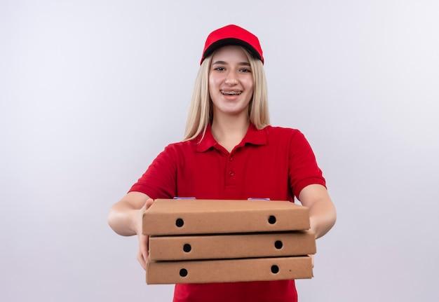 Uśmiechnięta dostawa młoda dziewczyna ubrana w czerwoną koszulkę i czapkę w ortezie dentystycznej, trzymając pudełko pizzy w aparacie na na białym tle