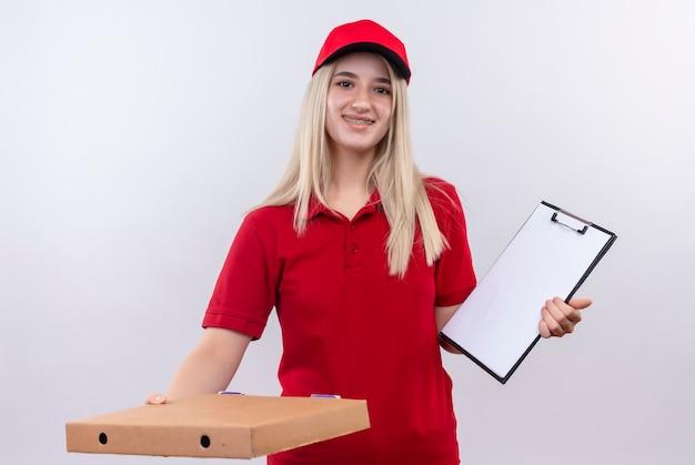 Uśmiechnięta dostawa młoda dziewczyna ubrana w czerwoną koszulkę i czapkę w ortezie dentystycznej trzymająca schowek i trzymająca pudełko po pizzy z aparatem na na białym tle