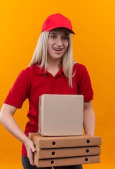 Uśmiechnięta dostawa młoda dziewczyna ubrana w czerwoną koszulkę i czapkę w stomatologicznym klamrze przytrzymującej pole i pudełko pizzy na na białym tle pomarańczowy