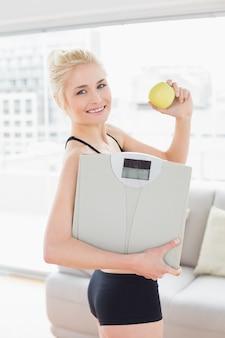 Uśmiechnięta dysponowana kobieta w sportswear mienia skala i jabłku