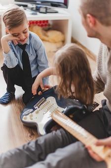 Uśmiechnięta dziecko patrząc na siostrę z gitarą
