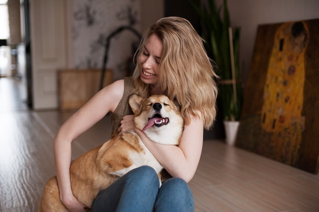 Uśmiechnięta dziewczyna bawić się z jej welsh corgi pembroke szczeniakiem, szczęśliwy śliczny pies