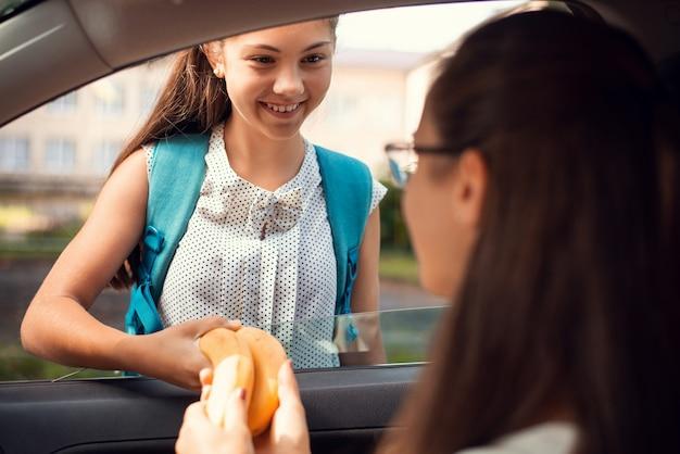 Uśmiechnięta dziewczyna bierze obiad od matki, która siedzi w samochodzie