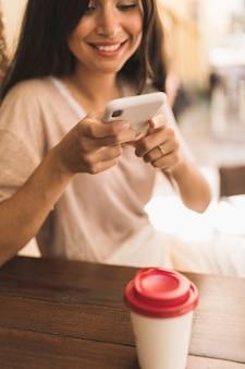 Uśmiechnięta dziewczyna bierze obrazek rozporządzalna filiżanka przez telefonu komórkowego