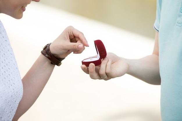 Uśmiechnięta dziewczyna biorąc jej pierścionek zaręczynowy