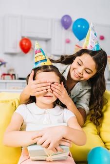 Uśmiechnięta dziewczyna chuje jej przyjaciela oczy trzyma prezenta pudełko w jej ręce