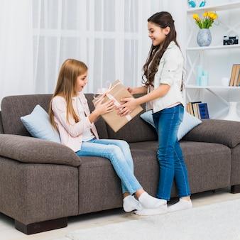 Uśmiechnięta dziewczyna daje teraźniejszości jej przyjacielowi siedzi na kanapie w domu