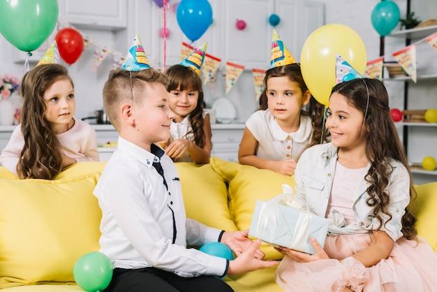 Uśmiechnięta dziewczyna daje teraźniejszości urodzinowa chłopiec w przyjęciu w domu