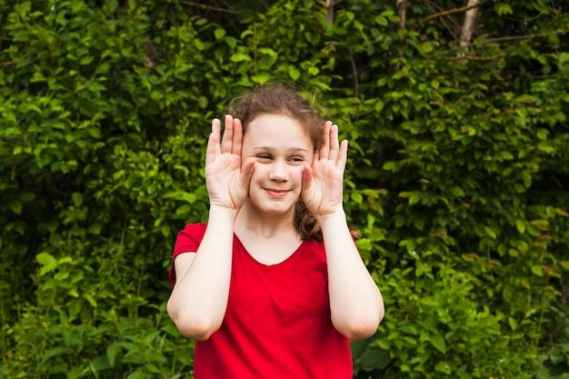 Uśmiechnięta dziewczyna dokucza z ręka gestem w parku