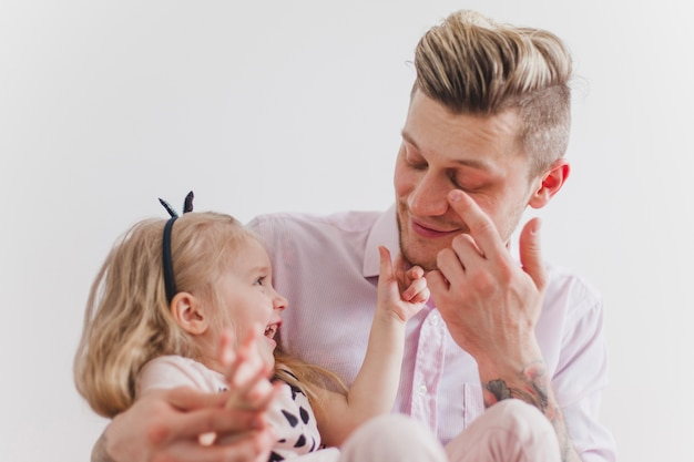 Uśmiechnięta dziewczyna dotyka jej ojca twarzy