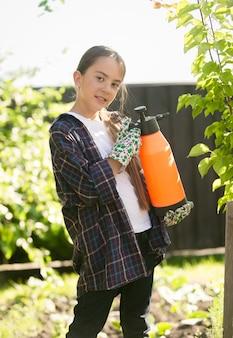 Uśmiechnięta dziewczyna eksterminująca owady w ogrodzie za pomocą toksycznego sprayu