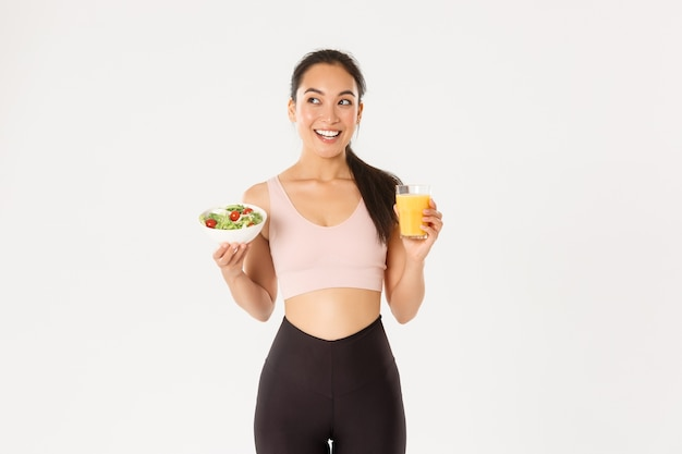 Uśmiechnięta dziewczyna fitness, azjatycka atletka wyglądająca na zadowoloną w lewym górnym rogu, jedząca zdrową sałatkę i sok pomarańczowy przed treningiem, schudnij z dietą.