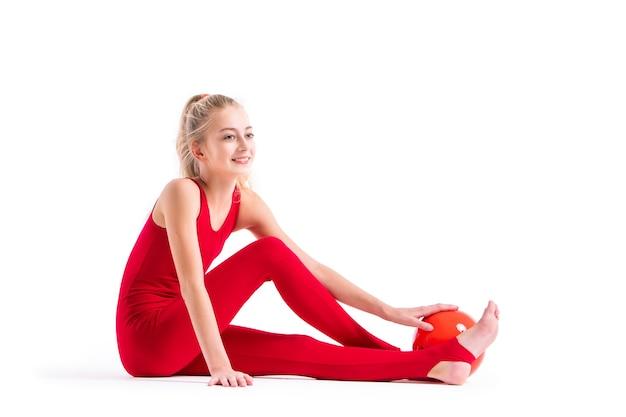 Uśmiechnięta dziewczyna gimnastyczka w czerwonym kombinezonie siedzi na białym tle