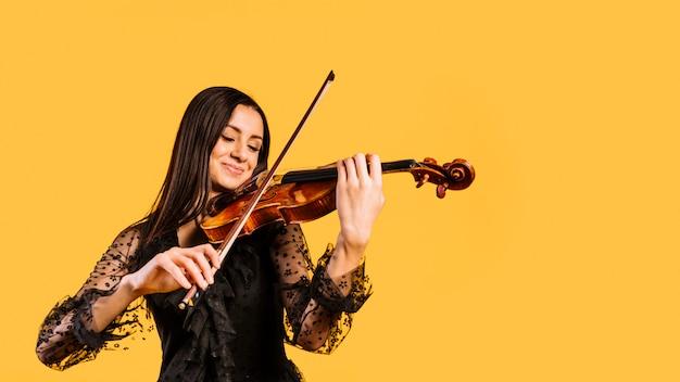 Uśmiechnięta dziewczyna gra na skrzypcach