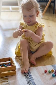 Uśmiechnięta dziewczyna gra w drewniane zdejmowane koraliki dla rozwoju motoryki małej maria montessori ma...