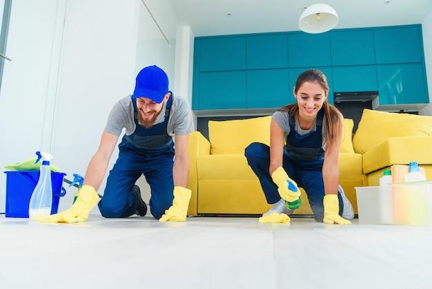 Uśmiechnięta dziewczyna i przystojny brodaty mężczyzna w odzieży roboczej, mycie parkietu środkami czyszczącymi i wycieranie szmatami