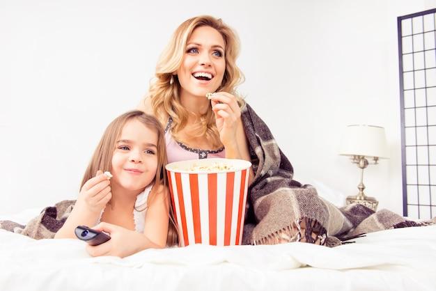 Uśmiechnięta dziewczyna je popcorn i ogląda bajki z matką